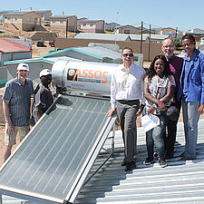 People are standing beside a solar panel