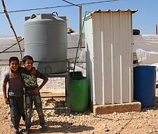 Children in front of a water tank